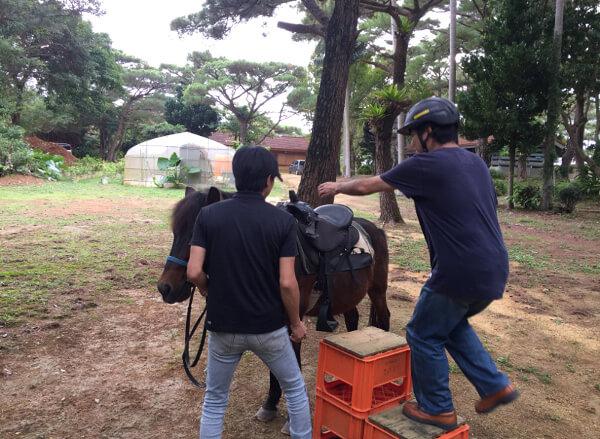 馬にまたがるための台に足をかけるところ