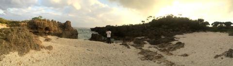 「ん」から始まる宮古島の方言を集めたTシャツを着ている夫と宮古島の海辺